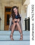 Small photo of Pretty brunette in tan pantyhose and open toe heels seated on steps with knees together while checking phone.