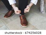 Man Hands Ties Up Shoelaces Of...