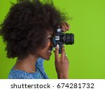 Small photo of portrait of a smiling pretty african american girl taking photo on a retro camera isolated over green background