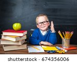 Small photo of Happy cute clever boy is sitting at a desk in a glasses with raising hand. Child is ready to answer with a blackboard on a background. First time to school. Back to school. Apple and books on desk