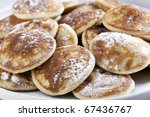 Dutch mini pancakes, or poffertjes, sprinkled with powdered sugar. - stock photo
