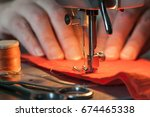 Small photo of Sewing machine's foot on a red fabric a background of women's hands (out of focus), Near lies skein of threads and scissors