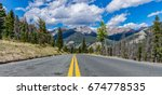 Riding the yellow line down a road in the Colorado Rockies  - stock photo