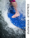 Small photo of Extreme close up of bare wet feet of male surfer wearing board shorts on blue textured rubber coated wake surfing board splashing on dark water spraying white sea foam spray of turbulent agitated wave