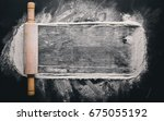 Small photo of Rolling pin and white flour on a dark background. Free space for text . Top view.