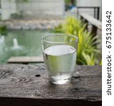 Small photo of Glass of clear and clear drinking water on wooden table in a garden restaurant background.