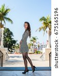 Small photo of Pretty backlit brunette in black pantyhose, short dress, and pumps standing side way over city downtown.