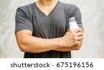 Small photo of Man holding a bottle of milk on gray background.