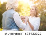 Small photo of Kind woman holding hands with grandmother in the park
