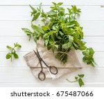 bunch of mint on a wooden... | Shutterstock . vector #675487066