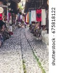 Small photo of KRUJE, ALBANIA - July 2017: Vintage and souvenir market street in historical town Kruje, Albania
