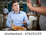 Stock photo customer in restaurant complaining to waitress about food 676151155