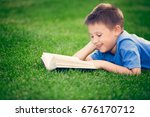 boy reading book  lying down on ... | Shutterstock . vector #676170712