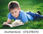 boy reading book  lying down on ... | Shutterstock . vector #676198192