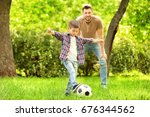 dad and son playing football... | Shutterstock . vector #676344562