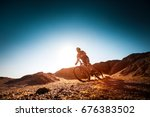 man rides bicycle in the dry... | Shutterstock . vector #676383502