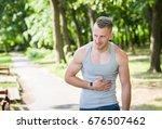 sport man stomachache in a park ... | Shutterstock . vector #676507462