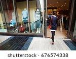 woman walking into a garment... | Shutterstock . vector #676574338