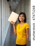 A portrait of a cute college student in yellow t-shirt thinking with a book against her head on a modern university campus.  Young female Asian Thai model late teens, early 20s of Chinese descent - stock photo