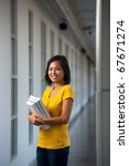 A beautiful happy college student in yellow t-shirt stands smiling in a hallway holding textbooks.  Young female Asian Thai model late teens, early 20s of Chinese descent looking at camera - stock photo
