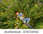 the boy lies in the meadow in... | Shutterstock . vector #676723432