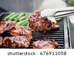 flipping a barbecued chicken... | Shutterstock . vector #676911058