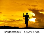 Small photo of Silhouette Scout director Show code on the mound at sunset.