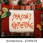 small pillow with season's greeting printed on it - stock photo