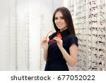 woman holding her glasses in... | Shutterstock . vector #677052022
