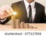 businessman hand putting coin... | Shutterstock . vector #677117836