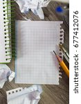 Small photo of Notepad with writing utensils lying in disarray