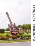 "Small photo of PUNTA CANA, DOMINICAN REPUBLIC - MAY 22, 2017: The signboard of the hotel and casino. Sculpture guitar ""Hard Rock"". Copy space for text"