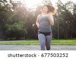 overweight woman running.... | Shutterstock . vector #677503252