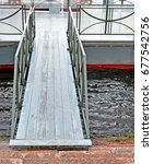 Small photo of Wooden gangway between embankment and floating mooring. Background.