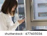 a woman using a smart phone at...   Shutterstock . vector #677605036