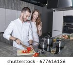 Small photo of cheerful couple in white and gray designer kitchen prepares a vegan meal. man is cutting tomatoes while woman has an objection to make it better. they are happy and enjoy their modern lifestyle