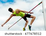 Small photo of high jump male athlete successful attempt over bar
