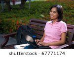 A cute college coed student sitting wearing pink shirt smiling and using her black laptop outside on a university campus bench. 20s female Asian Thai model of Chinese descent looking at camera - stock photo