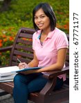 A cute college student wearing pink shirt smiling while studying outside on university campus bench surrounded by flowers.  20s female Asian Thai model of Chinese descent looking at camera - stock photo