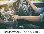 Asian Women press button on car radio for listening to music. - stock photo