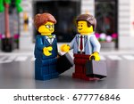 Small photo of Tambov, Russian Federation - June 22, 2017 Lego businessman and businesswoman with suitcases meet on the street. Studio shot.