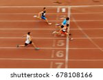 Small photo of blurred motion sprint finish of race athlete runners