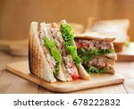 Small photo of tuna sandwich on wooden board