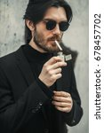 Small photo of White caucasian handsome bearded man in black suit and stylish glasses smoking cigarette on the street. Close up portrait. Vintage effect. Clothes advertising campaign concept.