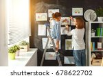Small photo of Mother and child girl hang their drawings on the wall