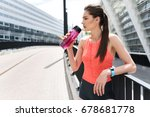 Stock photo pensive female runner drinking water outdoor 678681778