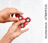 Small photo of Fidget spinner. Red hand spinner, boys playing with fidgeting hand toy. Stress relief. Anti stress and relaxation adhd attention fad boy concept.