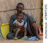 Small photo of FERLO DESERT, SENEGAL - APR 25, 2017: Unidentified Fulani man sits on the ground near the shack with his daughter. Fulanis (Peul) are the largest tribe in West African savannahs