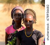 Small photo of FERLO DESERT, SENEGAL - APR 25, 2017: Unidentified Fulani girl in headscarf and colored clothes stands on the street. Fulanis (Peul) are the largest tribe in West African savannahs