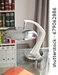 Small photo of A chrome silver fashionable table lamp in an airy light office setting.